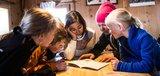 Kinder lesen gemeinsam ein Buch mit der Lehrerin beim Mittagsessen