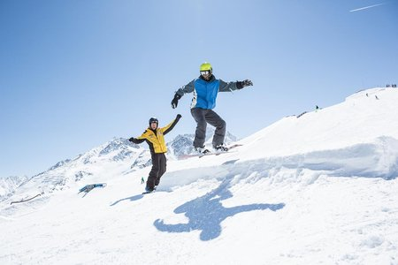 Snowboarder springt von einer Mini-Schanze